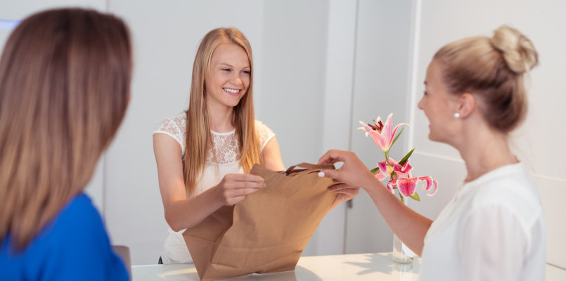 Smiling attractive young shop assistant serving customers in a store handing over a brown paper packet over the counter with a lovely smile